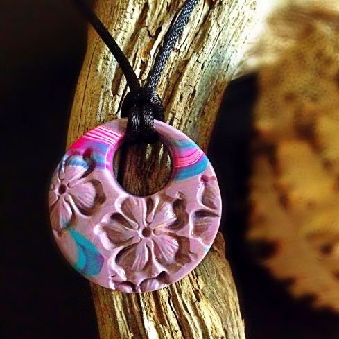Finished stamped Hawaiian floral Polymer clay pendant on a satin cord listed in my Etsy store.